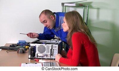 IT specialist man repairing her colleague computer in...