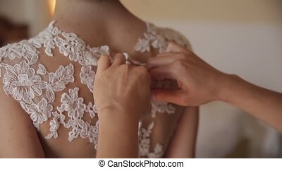 Wedding Bride mother fastens with buttons on the dress
