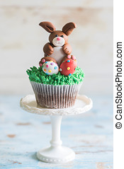 Bunny with Easter eggs on the top of cup cake,selective...