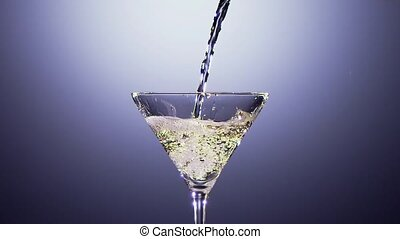 Alcohol drink is poured into tall martini glass. Slow motion...