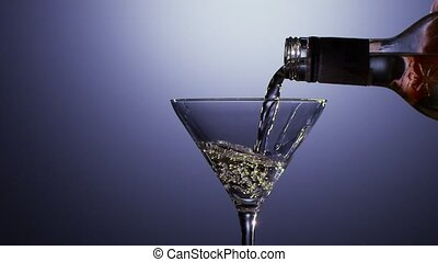 Alcohol drink poured into martini glass of bottle. Slow...