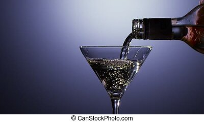 Slow motion. Alcohol drink poured into martini glass of...