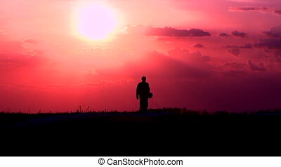 Military fighter pilot walking against the setting sun, keeping helmet in his hands during sunset