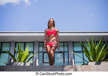 young sexy beautiful woman in pink bikini, posing on terrace of resort hotel, slim, tanned skin, fashion glamour, relaxed, smiling, sensual, summer vacation