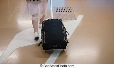 Young female traveler walking through the airport with...