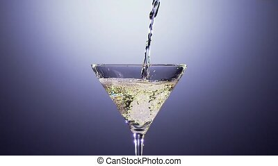 Alcohol beverage is poured into tall martini glass. Slow...
