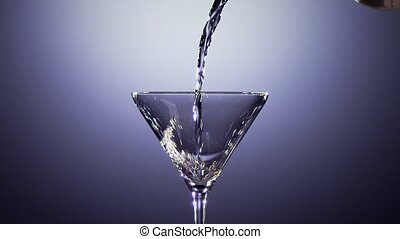 Slow motion. Alcohol drink is poured into tall martini glass...