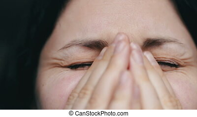 Close up portrait of upset woman with tears closes face with...