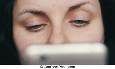 Beautiful green-eyed girl looks in a white smart phone close up view