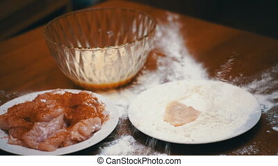 Piece of Meat Falls on a Plate of Flour in Home Kitchen....