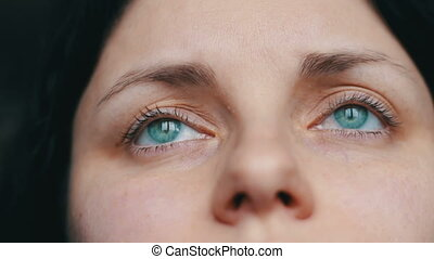 Green-eyed female face looks away and to the camera. close-up view with sad girl