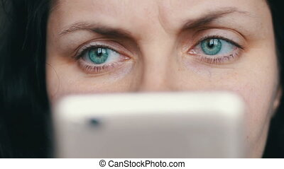 Beautiful angry green-eyed girl looks in a white smart phone close up view