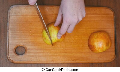 Woman Hands with a Knife Sliced Apple on a Wooden Kitchen...