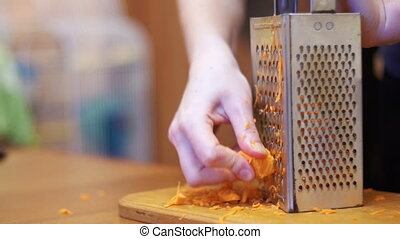 Woman Hands Rubbing Carrots on Grater in a Home Kitchen....