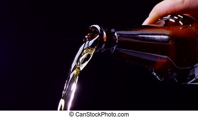 Beer is poured from dark glass bottle. Slow motion, closeup...