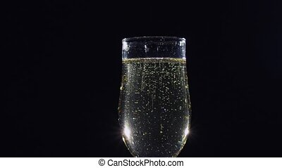 Bubbles of sparkling champagne wine in a glass. Slow motion...