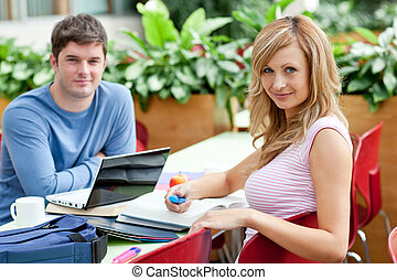 Smiling couple of students working together in the cafeteria...