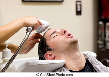 Young caucasian man having his hair washed in a hairdressing...