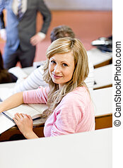 Portrait of a caucasian female student during a university lesson in an auditorium