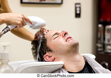 Cute man having his hair washed in a hairdressing salon