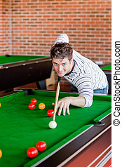 Assertive young man playing snooker in a club