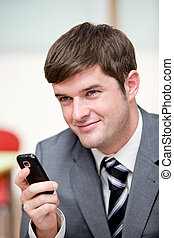 Portrait of an assertive businessman sending a text message with his cellphone in his office at work