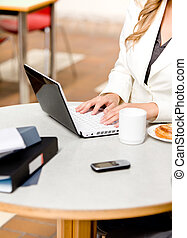 Close-up of a busy businesswoman using her laptop with...
