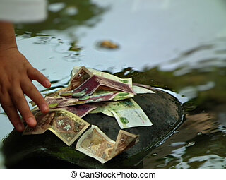 Money Turtle - a persom placing chinese money on a turtle...