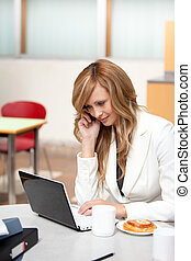 Busy businesswoman with laptop, coffee and food talking on phone in her office