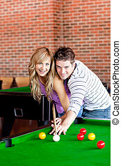 Young couple playing pool in a club