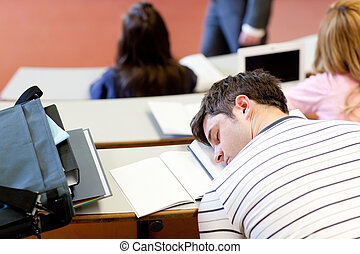Asleep male student during an university lesson in an...