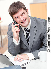 Charismatic businessman using his laptop while talking on phone