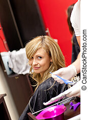 Smiling blond woman drying her hair in a hairdressing salon