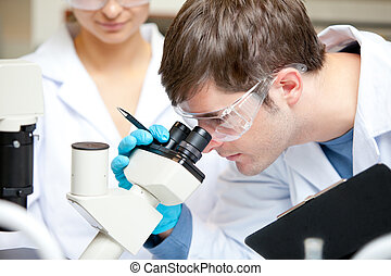 Caucasian male scientist holding pen and clipboard looking...