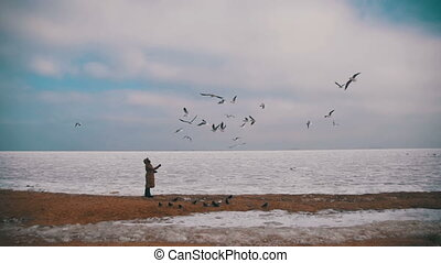 Woman Feeds the Hungry Seagulls Flying over the Frozen Ice-Covered Sea. Slow Motion