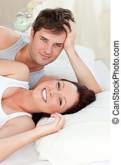 Radiant caucasian couple lying on bed in their bedroom
