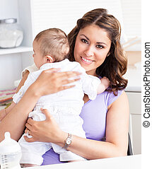 Young mother holding her sweet baby - Smiling young mother...