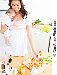 Beautiful mother preparing food for her adorable baby in the...