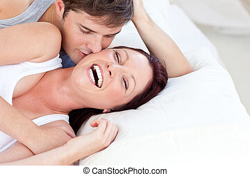 Affectionate caucasian couple lying on bed in their bedroom