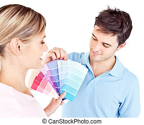 Enamored couple choosing color for a room in their new house