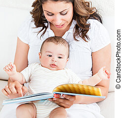 Bright mother showing images in a book to her cute little...