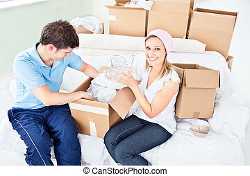 Concentrated young couple unpacking boxes with glasses in...