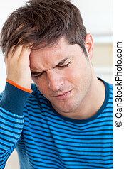 Cute man having a headache in the living-room at home