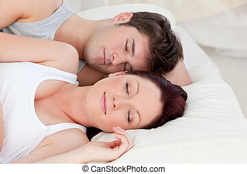 Enamored young couple sleeping in bed together