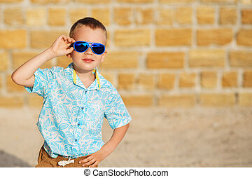 little boy wearing blue mirror sunglasses against the yellow...