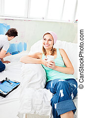 Relaxing smiling woman sitting on the sofa looking at the camera while her boyfriend is painting the room
