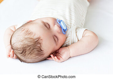 Portrait of an adorable baby with a pacifier sleeping in a...