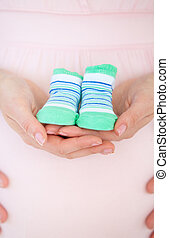 Close-up of a caucasian pregnant woman holding baby shoes...