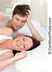 Glowing caucasian couple lying on bed in their bedroom