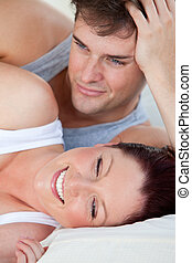 Portrait of a young pregnant woman and of her husband lying on the bed at home